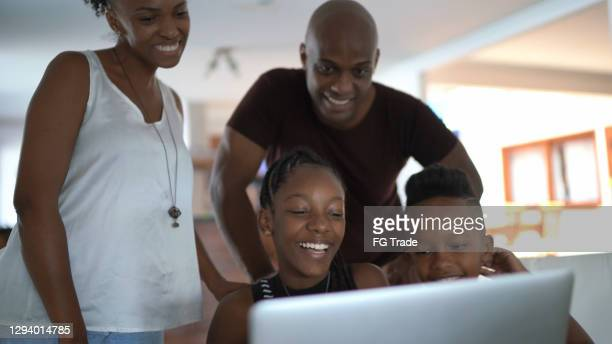 familie, die einen videoanruf mit laptop zu hause macht - mother daughter webcam stock-fotos und bilder