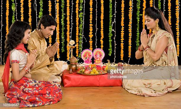 family doing diwali pooja - goddess lakshmi stock photos and pictures