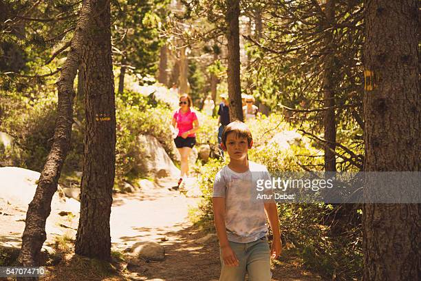 Family doing hiking in the Catalan Pyrenees mountains during the summer vacations with beautiful woodland.