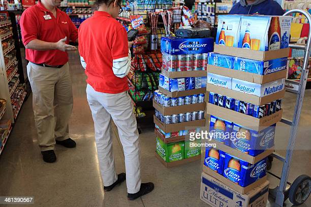 Family Dollar employees left receive cases of beer from a bulk delivery man at a Family Dollar Stores Inc location in Mansfield Texas US on Tuesday...