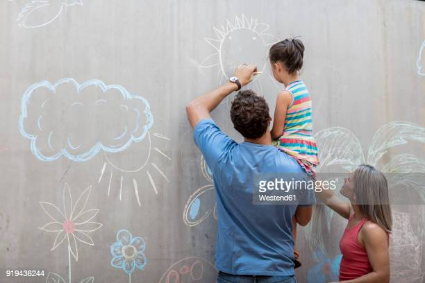 Family drawing colourful pictures with chalk on a concrete wall