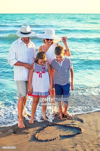 Famille de dessin de coeur dans le sable