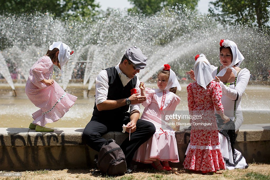 A family dressed as 'chulapos' have some food during the San Isidro festivities at Pradera de San Isidro park on May 15, 2014 in Madrid, Spain. During the festivities in honor of San Isidro Labrador in Madrid revelers take the streets and enjoy music and popular food. Chulapos or Goyescos dance the regional dance known as 'chotis' wearing traditional costumes of Madrid.