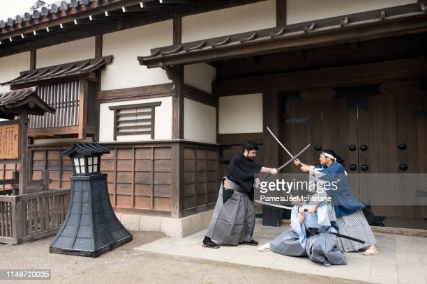 family dressed as samurai, sword fighting in japanese village, kyoto - resilience stock photos and pictures
