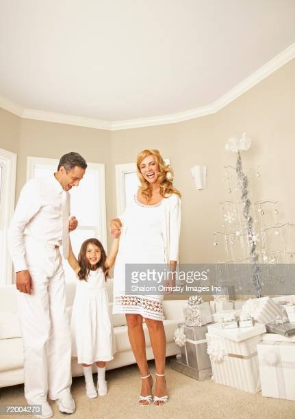 Family dressed in all white next to gifts and artificial Christmas tree