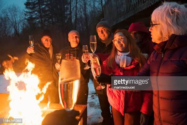 """familj dricker champagne bredvid en brand utomhus på vintern - """"martine doucet"""" or martinedoucet bildbanksfoton och bilder"""