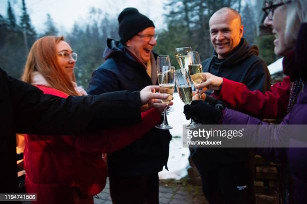 """family drinking champagne beside a fire outdoors in winter - """"martine doucet"""" or martinedoucet stock pictures, royalty-free photos & images"""