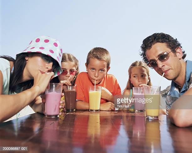 family drinking milkshakes, portrait - lunettes de soleil teintées photos et images de collection