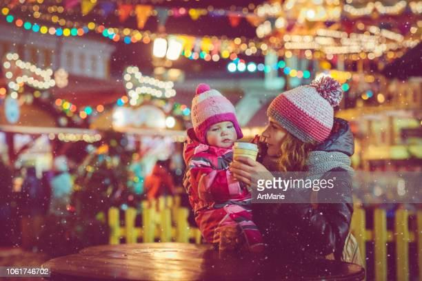 都市のクリスマス マーケットにお茶を飲む家族