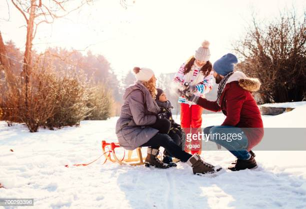 Family Drinking Tea Outdoors At Winter