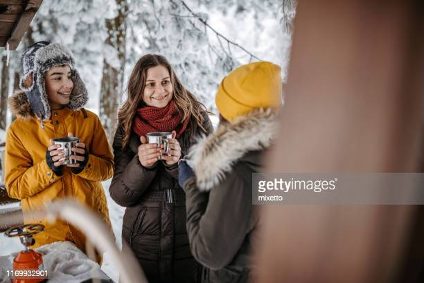 family drinking tea outdoors at winter time - knit hat stock pictures, royalty-free photos & images