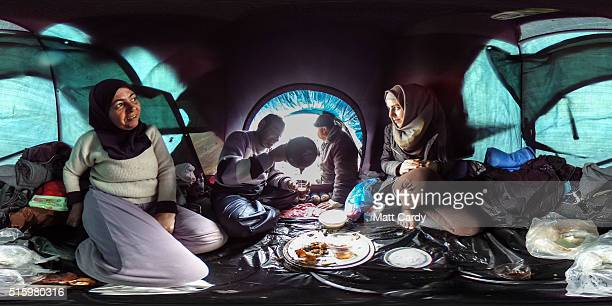 A family drinks tea inside their tent at the Idomeni refugee camp on the Greek Macedonia border on March 16 2016 in Idomeni Greece The decision by...