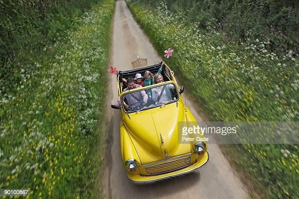 family driving in open top car down country lane - convertible stock pictures, royalty-free photos & images