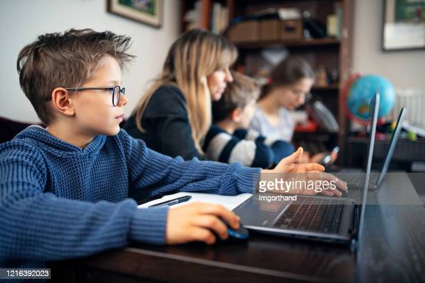 family during covid-19 quarantine attending to online school class. - homeschool stock pictures, royalty-free photos & images