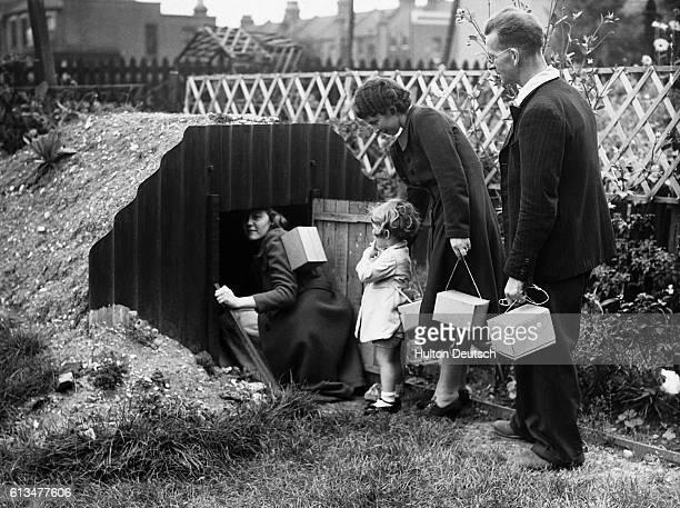 A family each carrying their gas masks in a little box enter the dugout air raid shelter in their garden 1939