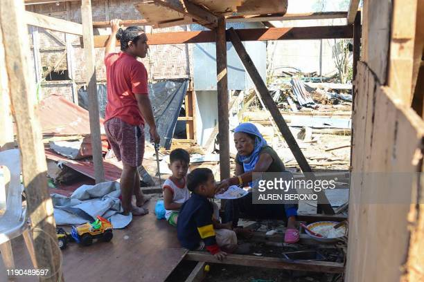 Family eat a meal inside their house damaged at the height of Typhoon Phanfone in Guiuan town in Eastern Samar province on December 26, 2019. -...