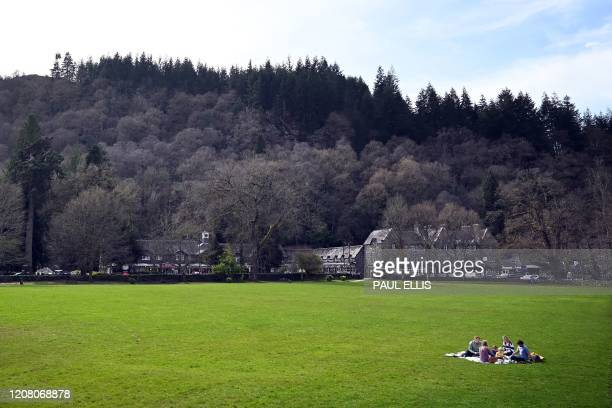Family eat a picnic on the playing field at Betws-y-Coed in north Wales on March 23, 2020. - Prime Minister Boris Johnson warned on Sunday he may...