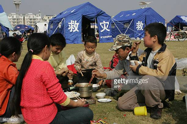 A family eat and camp outdoors along with thousands of other residents 27 November 2005 to avoid aftershocks after the 26 November 57 earthquake in...