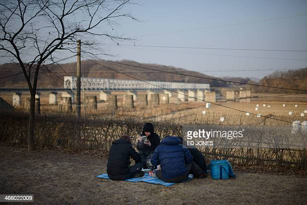 A family eat as they sit before the Freedom Bridge following a memorial ceremony for relatives in North Korea near the Freedom Bridge at the...