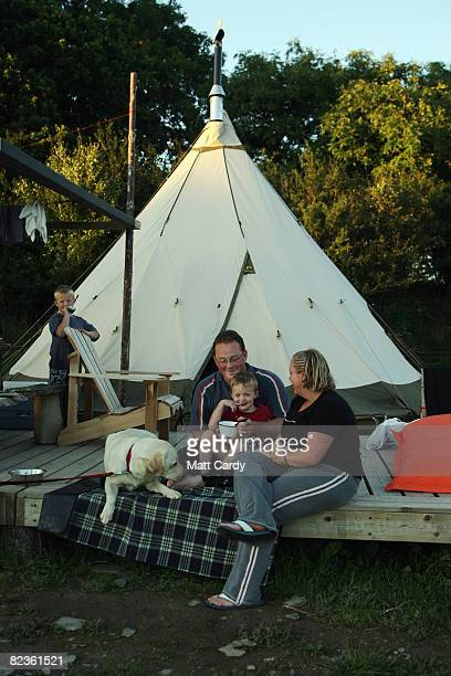 A family eat their evening meal outside their tipi at the Fforestcamp on August 14 2008 near Cardigan in Pembrokeshire Wales Despite the dismal...