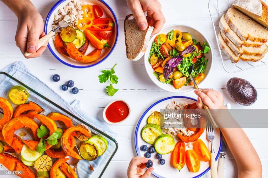Family eating a healthy vegetarian food. Vegan lunch table top view, plant based diet. Baked vegetables, fresh salad, berries, bread on a white background. : Stock Photo