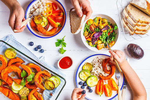 Family eating a healthy vegetarian food. Vegan lunch table top view, plant based diet. Baked vegetables, fresh salad, berries, bread on a white background. 1083417790