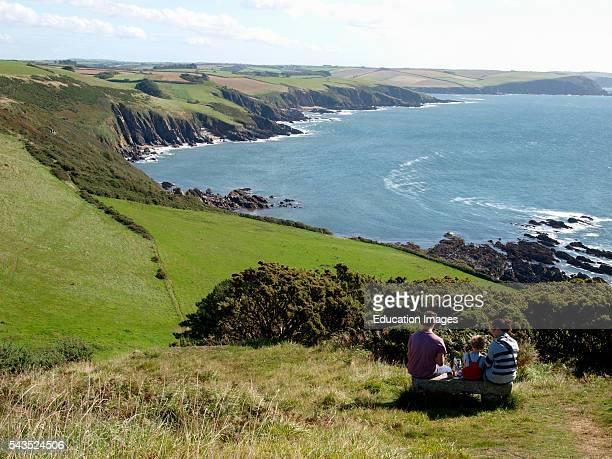 Family eating a picnic along the southwest coast path near Noss Mayo Devon UK