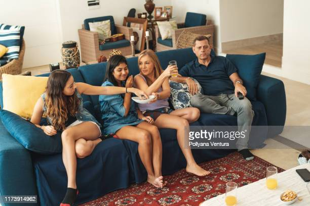 family eating and watching television in living room - snack stock pictures, royalty-free photos & images