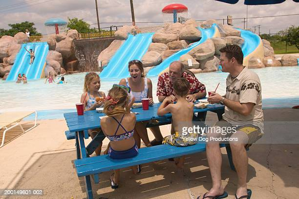 family  eating at table in water park - dog eats out girl stock pictures, royalty-free photos & images