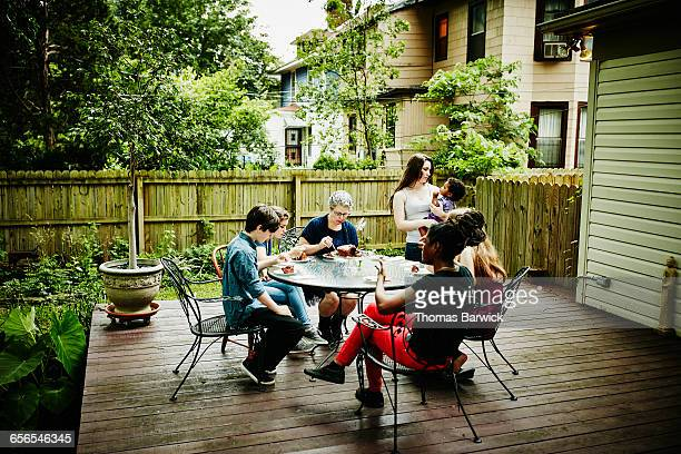 Family eating birthday cake together on patio