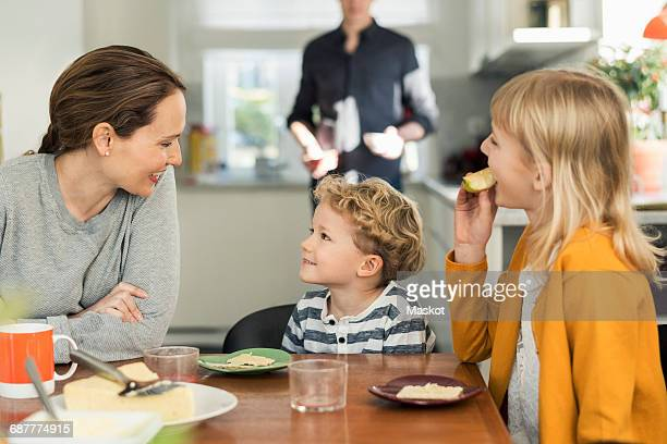 Family eating breakfast at dining table in living room