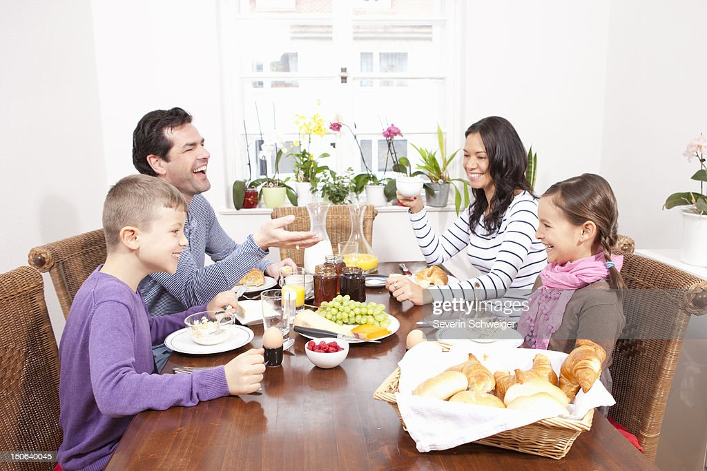 Family eating breakfast at table : Stock Photo