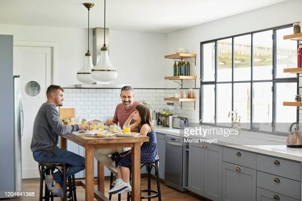 自宅のキッチンで朝食を食べる家族 - ホモセクシャル ストックフォトと画像