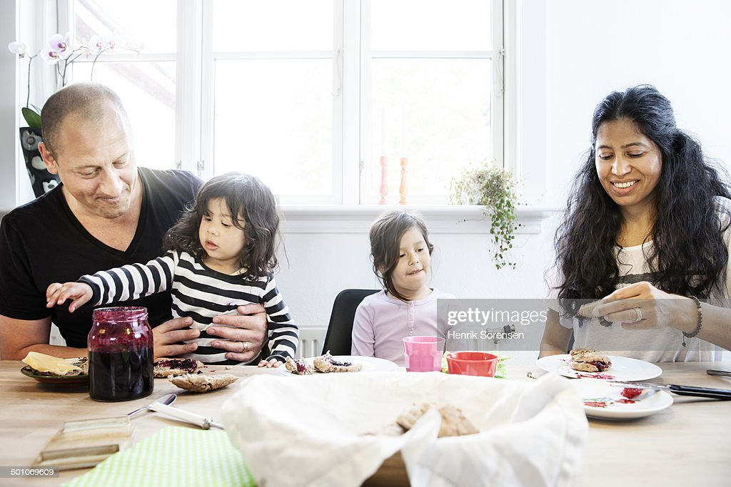 A family eating breakfast together, parents helping children preparing their food