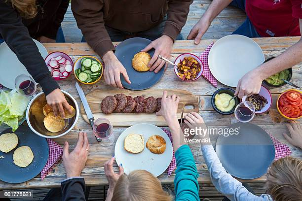 Family eating burgers at beer table