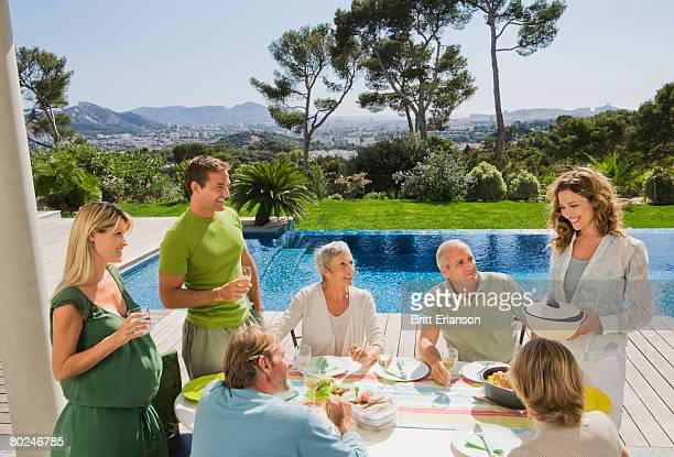 Family eating by poolside.