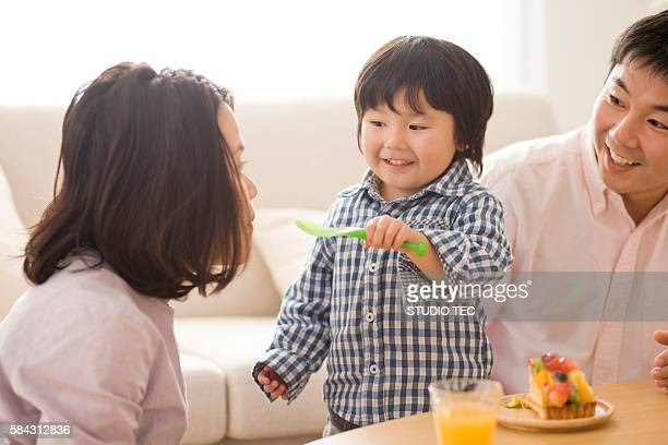 Family eating cake in living room