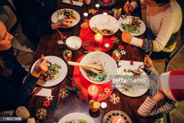 family eating christmas dinner - evening meal stock pictures, royalty-free photos & images