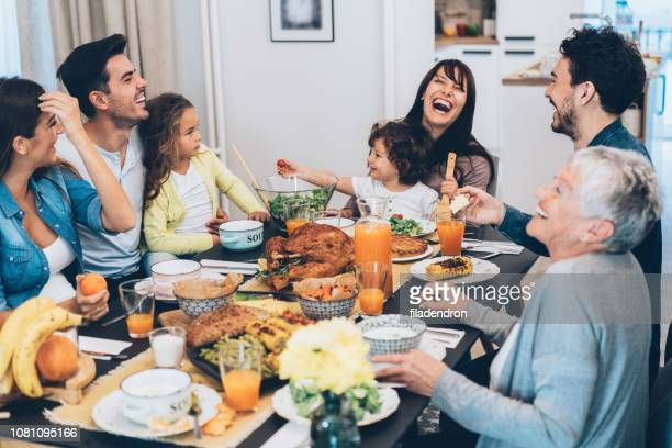 family eating christmas lunch - thanksgiving holiday stock pictures, royalty-free photos & images