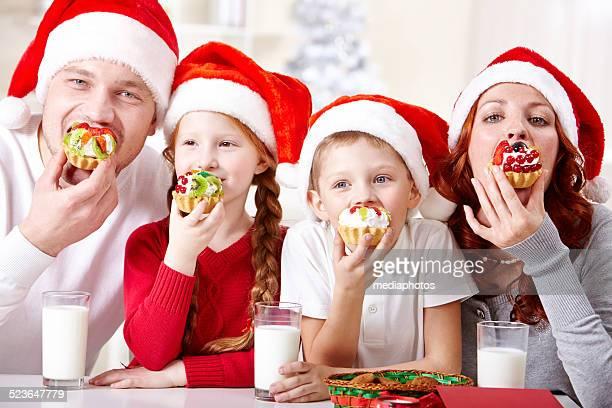 Familia comiendo Navidad sabrosos cupcakes