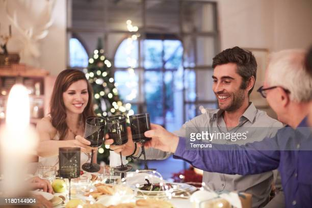 family eating dinner and  toasting together on new year's eve. - brindisi capodanno foto e immagini stock