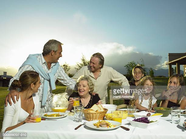 Family eating dinner around outdoor table