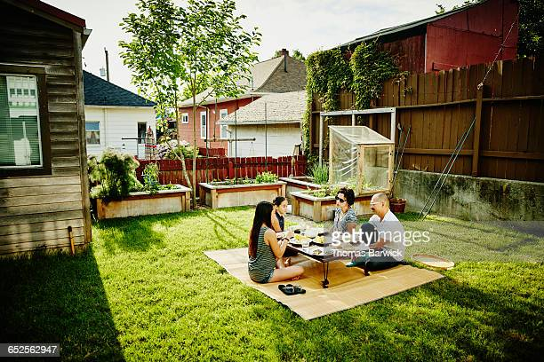 Family eating dinner in backyard on summer evening