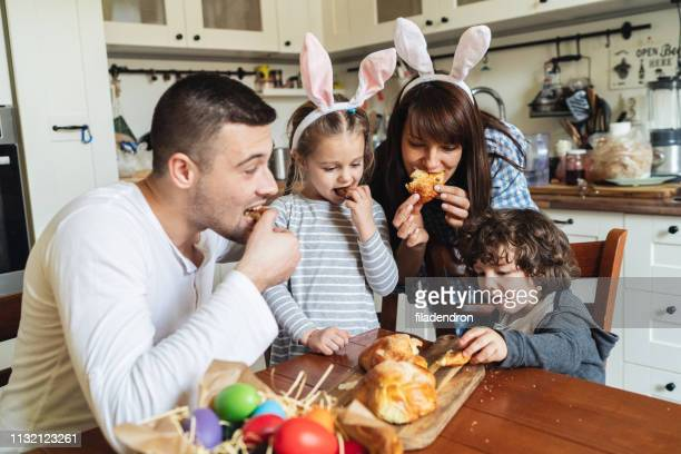 family eating easter bread - easter cake stock pictures, royalty-free photos & images