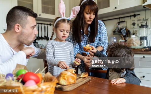 family eating easter bread - easter religious stock pictures, royalty-free photos & images