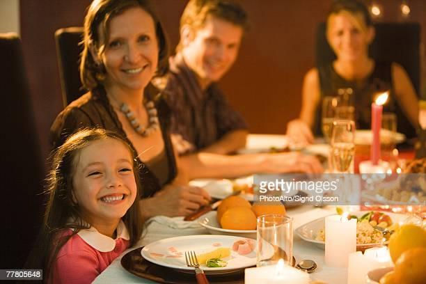 Family eating festive dinner, looking toward camera, smiling