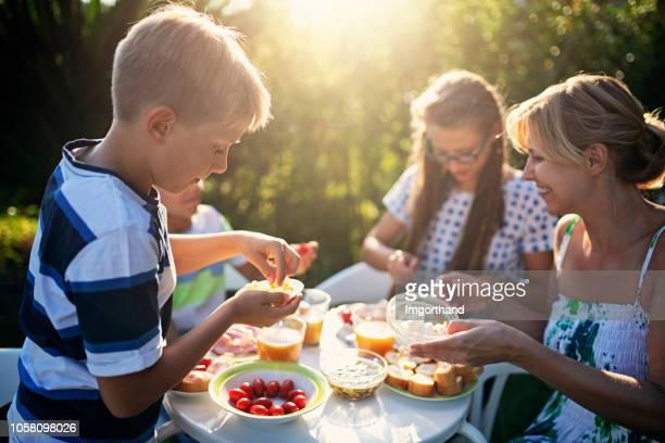 familie eten vers ontbijt buitenshuis - ontbijt stockfoto's en -beelden