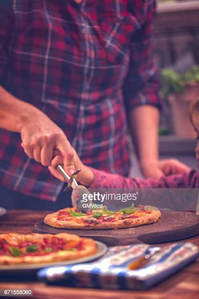 family eating homemade pizza at home - comfort food stock pictures, royalty-free photos & images
