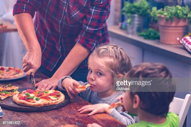 family eating homemade pizza at home - pizza margherita foto e immagini stock