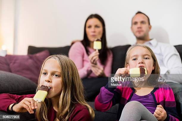 Family eating ice cream in living room